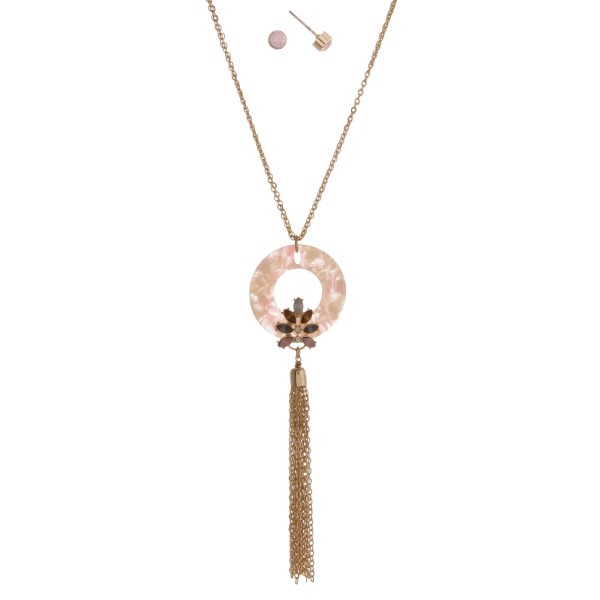 """Long gold tone necklace with acetate pendant accent with rhinestones and a chain tassel. Approximately 32"""" in length."""