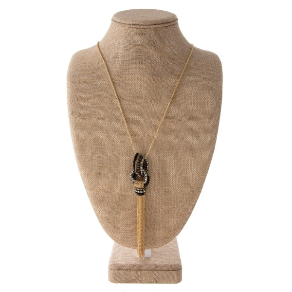 """Long necklace with faceted bead knot detail and metal tassel. Approximately 32"""" in length with 4"""" tassel."""