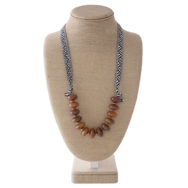 "Adjustable ribbon necklace with large bead details. Approximately 42"" in length."