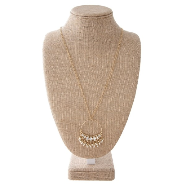 "Long necklace with circle pendant accents with rhinestone and pearls. Approximately 32"" in length with a 2.5"" in length."