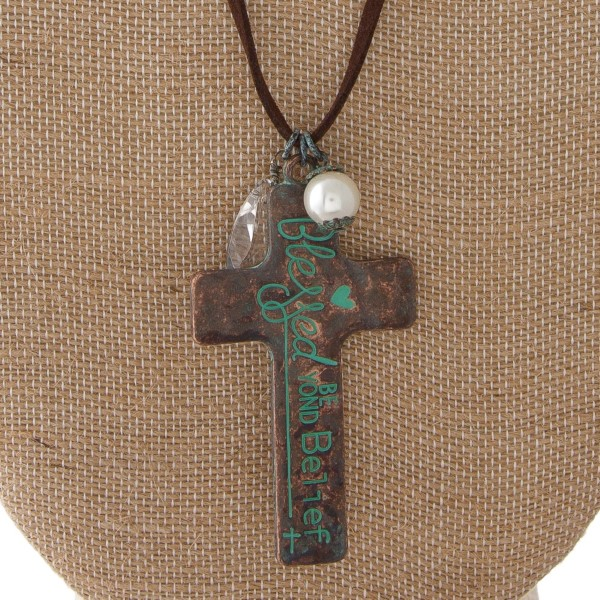 """Long necklace with faux leather cord and metal cross pendant stamped with """"Blessed Beyond Belief."""" Approximately 32"""" in length with a 2"""" pendant."""