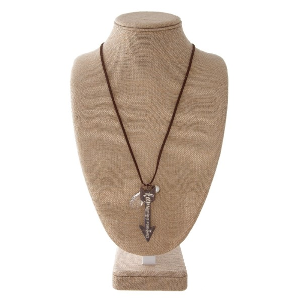 """Long necklace with faux leather cord and metal arrow pendant stamped with """"Keep Moving Forward."""" Approximately 32"""" in length with a 2"""" pendant."""