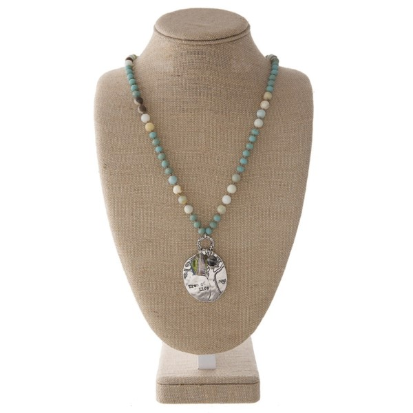 """Long necklace with faceted and natural stone beads and an oval pendant stamped with. Approximately 32"""" in length with a 2"""" pendant."""