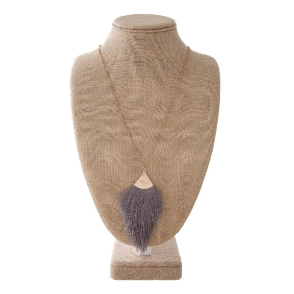 """Long gold metal necklace featuring a dark grey tassel pendant. Pendant approximately 4"""". Approximately 38"""" in length overall."""