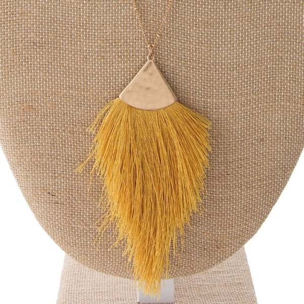 "Gold tone necklace with a soft, thread tassel pendant. Approximately 32"" in length."