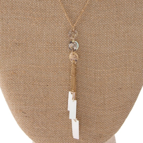 """Long gold tone necklace with natural shell details and iridescent accents. Approximately 32"""" in length with a 3"""" tassel."""