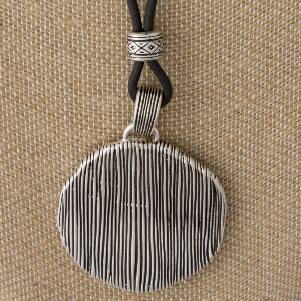 """Cord necklace with circle pendant. Approximately 20"""" in length with a 2"""" pendant."""