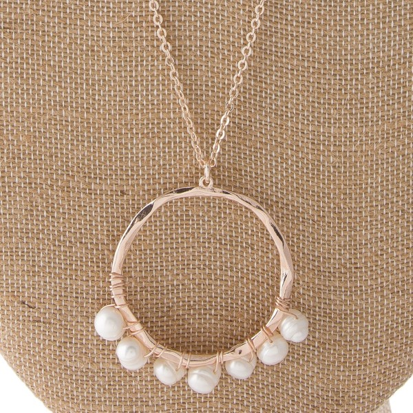 "Long metal necklace with circle pendnat accented with wire wrapped pearl. Approximately 32"" in length with a 1.5"" in diameter pendant."