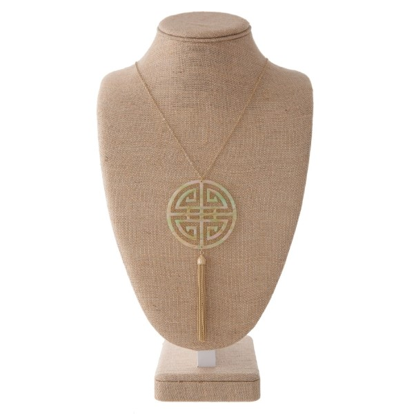"""Long gold tone necklace with boho pendant and metal tassel. Approximately 32"""" in length with a 2.5"""" pendant and 3"""" tassel."""