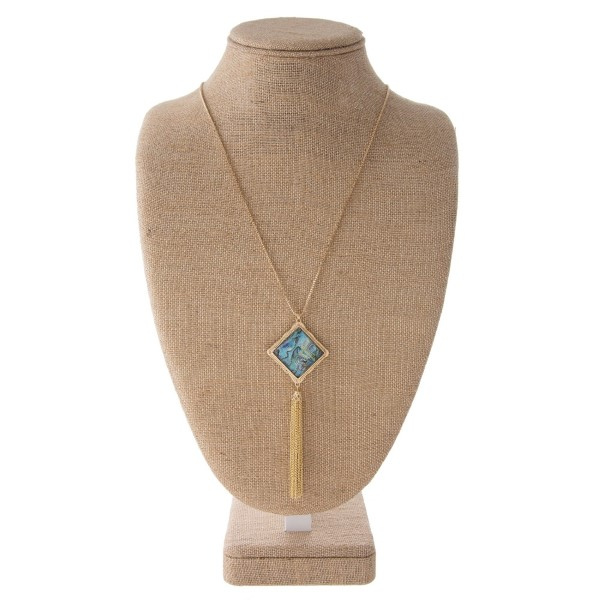 """Long gold tone necklace with square pendant and metal tassel. Approximately 32""""in length with a 2.5"""" tassel."""
