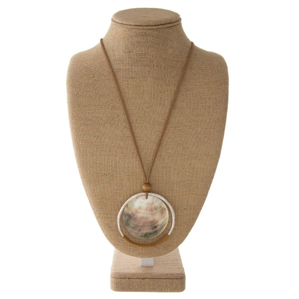 """Long leather cord necklace with metal and mother of pearl circle pendant. Approximately 34"""" in length with a 3"""" pendant."""