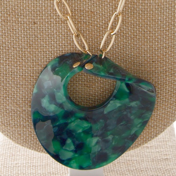 """Gold tone chain necklace with twisted circle acetate pendant. Approximately 30"""" in length with a 2.5"""" pendant."""