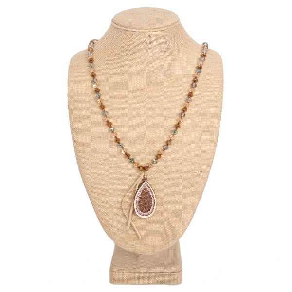 "Long faceted bead necklace with wooden pendant detailed with glitter and rhinestones. Approximately 32"" in length."