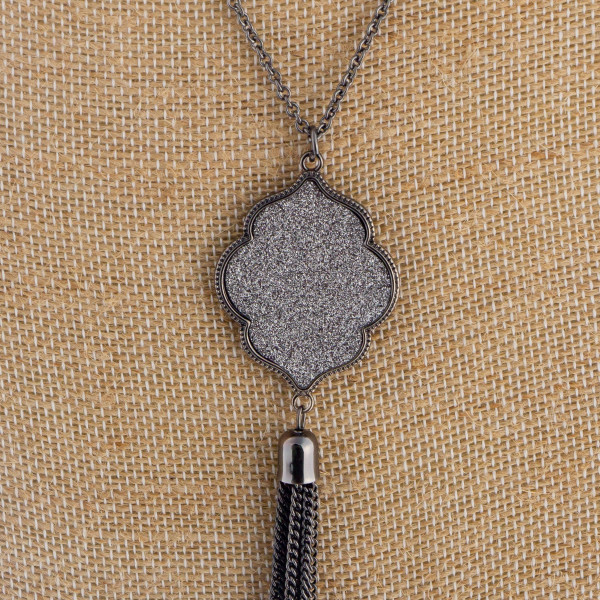 "Long metal necklace featuring a glitter moroccan shaped pendant with tassel. Approximate 36"" in length with a 4.5"" pendant."