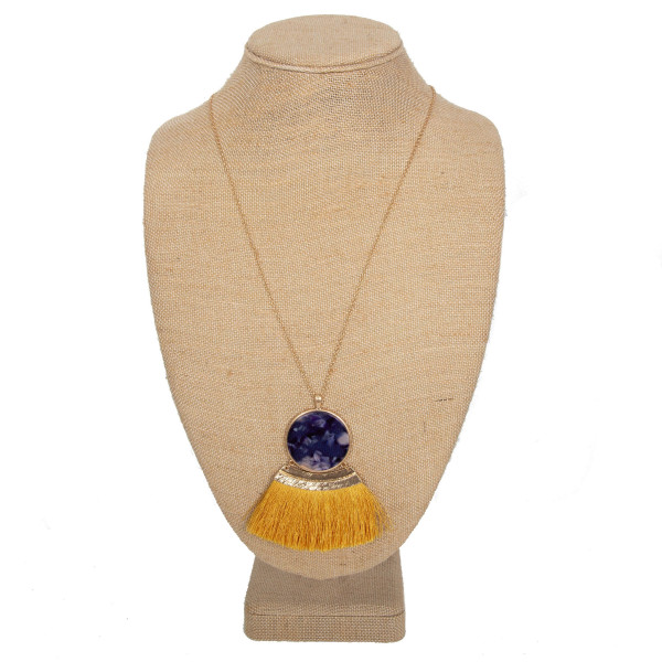 """Long necklace with acetate circle with fanned tassel. Approximately 32"""" in length with a 3"""" pendant."""