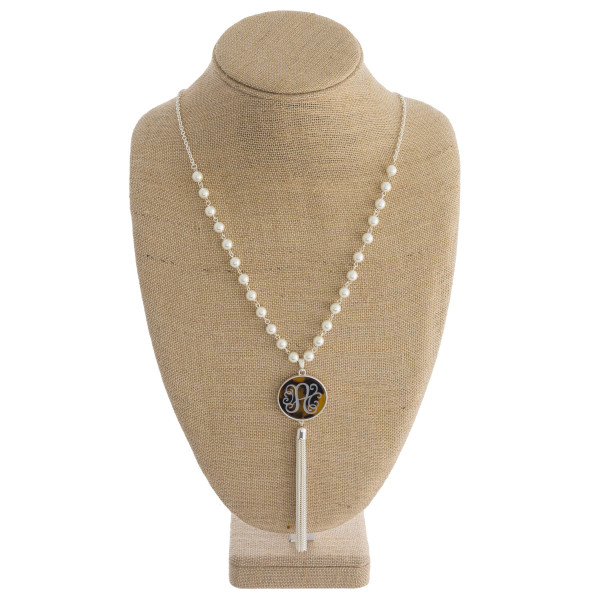 "Long necklace with tortoise monogram pendant and pearl detail. Approximately 33"" in length."