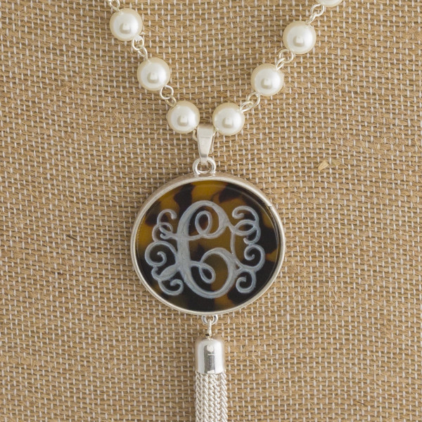 """Long necklace with tortoise monogram pendant and pearl detail. Approximately 33"""" in length."""