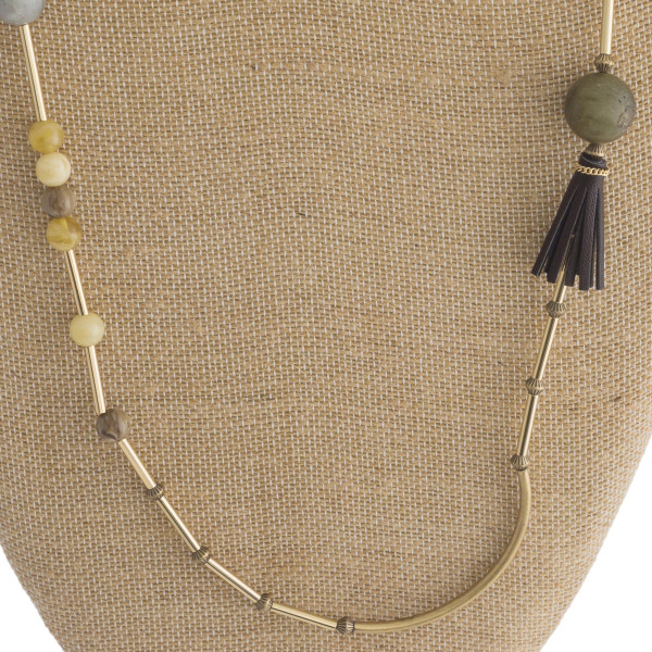 Long gold metal linked necklace with tassel detail.