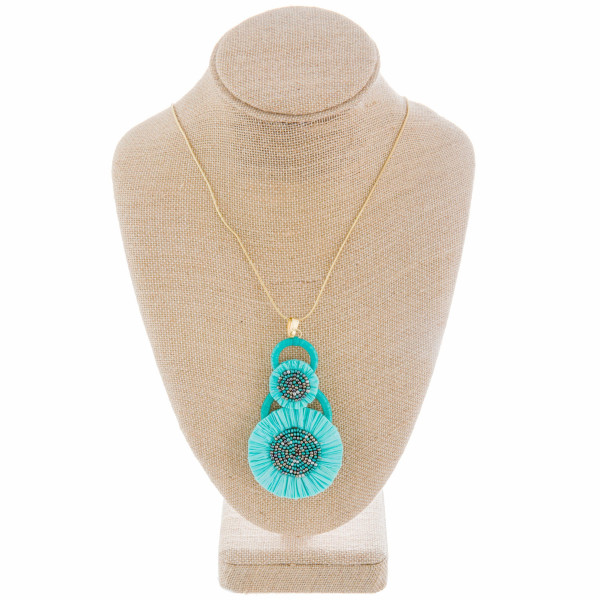 """Long metal necklace with bead details and raffia pendant. Approximate 37"""" in length."""
