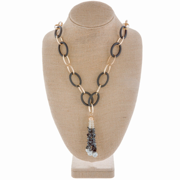 "Gorgeous wood and gold metal chained linked necklace with natural stone and bead tassel pendant. Approximate 38"" in length."