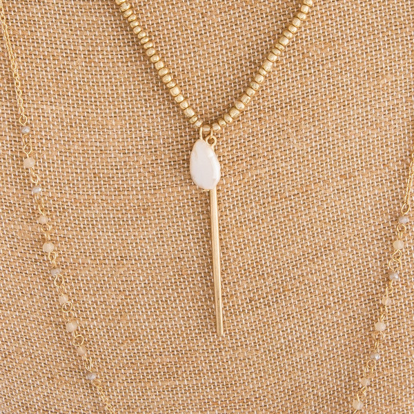 "Long beaded gold necklace with pearl details. Approximate 34"" in length."
