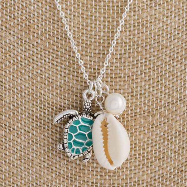 "Long metal necklace featuring a turtle detail, puka shell, and pearl accents. Approximately 18"" in length."