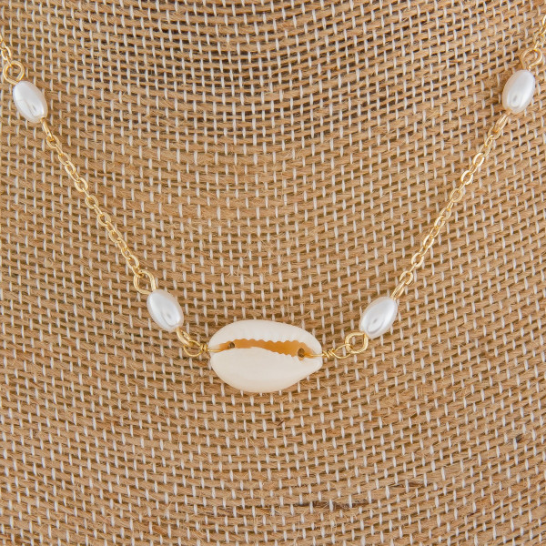 Short metal necklace with pearl beads and seashell pendant.