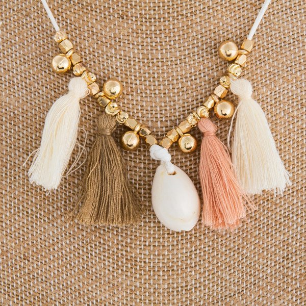 "Long braided fabric necklace with tassels and sea shell pendant. Approximate 18"" in length."