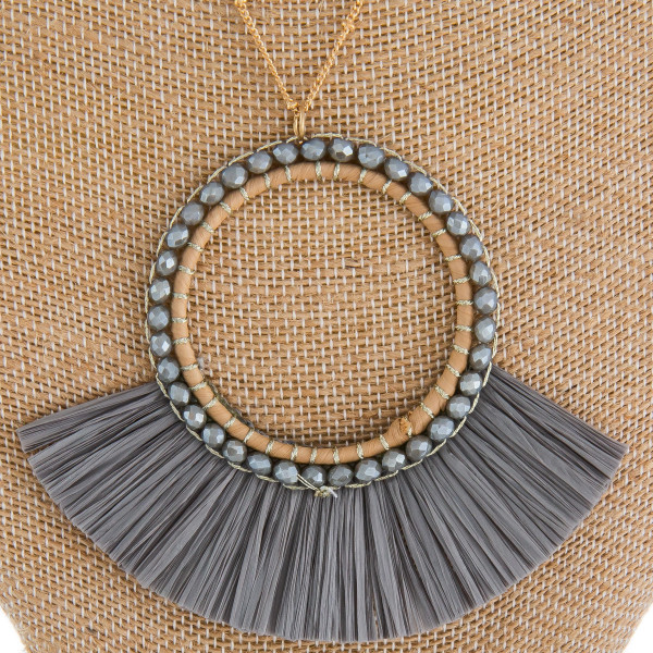 "Long metal necklace with beads and raffia tassel pendant. Approximate 34"" in length."