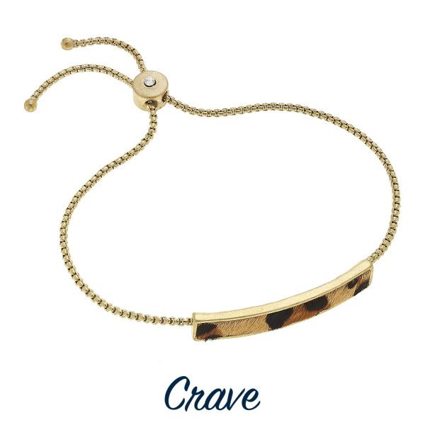 Gold tone adjustable leopard print bangle bracelet with rhinestone closure detail.