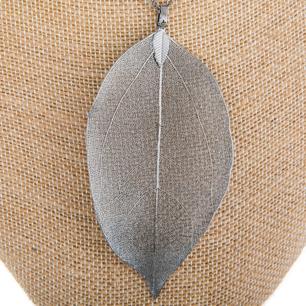 """Long metal necklace with leaf shaped pendant. Approximately 32"""" in length."""