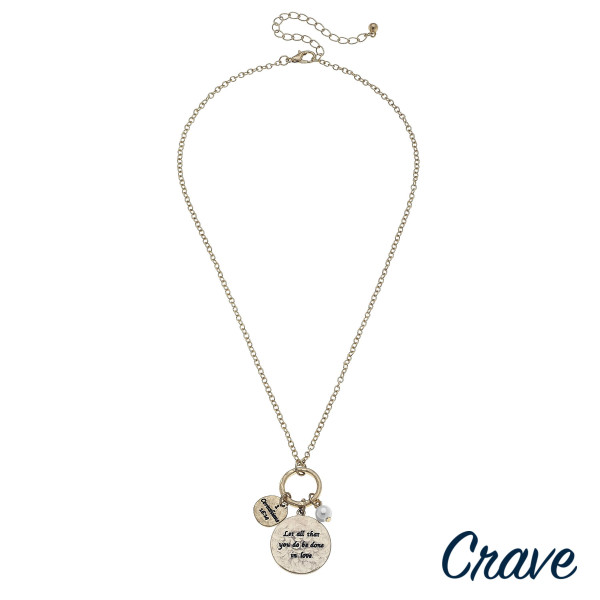 """Gold metal necklace featuring a circular pendant with """"Let All That You Do Be Done In Love"""" inspiring message, and a pearl accent. Pendant approximately 1.5"""". Approximately 18"""" in length."""