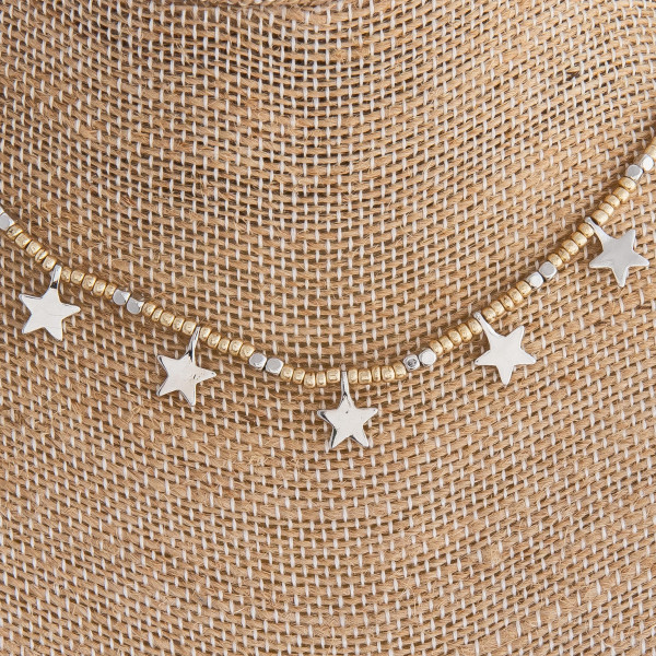 "Gold beaded necklace featuring gold and star accents. Approximately 16"" in length."