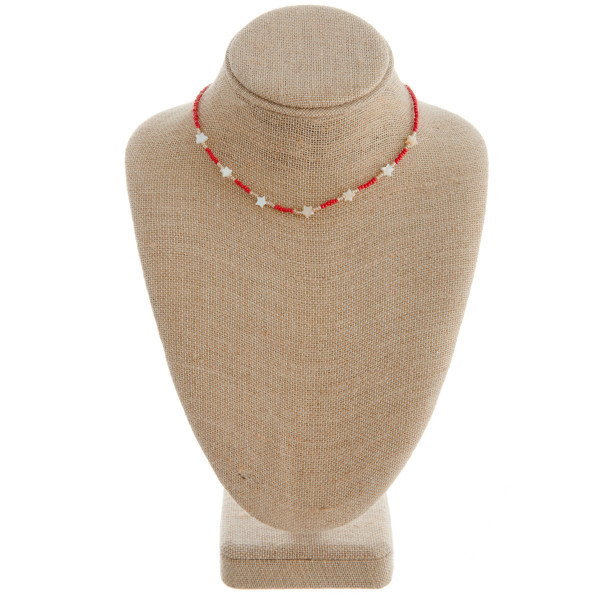 "Red beaded necklace featuring gold and star accents. Approximately 16"" in length."