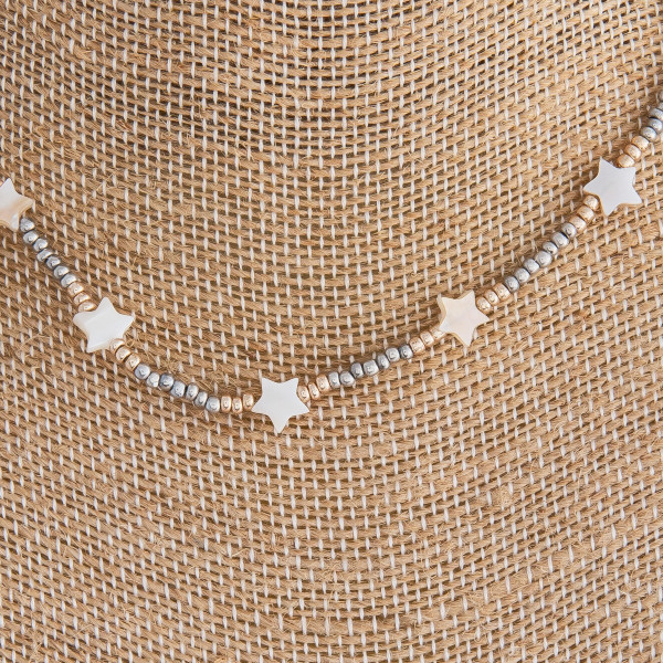"Silver beaded necklace featuring gold and star accents. Approximately 16"" in length."