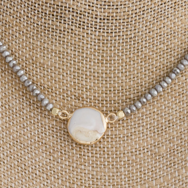 "Grey beaded necklace featuring mother of pearl detail and a lobster clasp closure. Approximately 16"" in length."