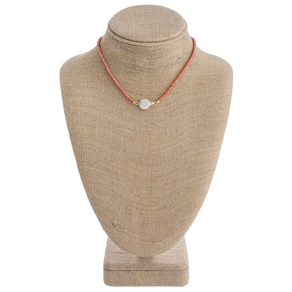"Peach beaded necklace featuring mother of pearl detail and a lobster clasp closure. Approximately 16"" in length."