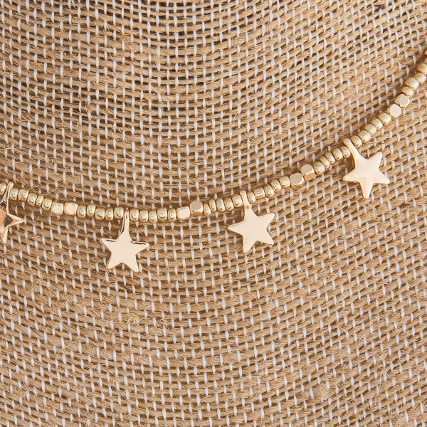 "Gold beaded necklace featuring gold star accents. Approximately 16"" in length."