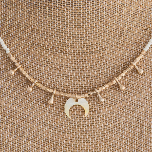 """White beaded necklace featuring crescent and gold accents. Approximately 16"""" in length."""