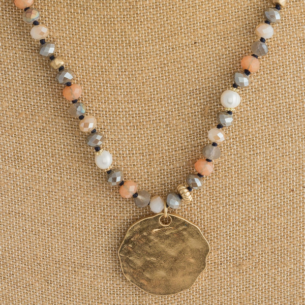 "Long beaded necklace featuring a circular metal pendant with pearl accents. Pendant approximately 1.5"" in diameter. Approximately 38"" in length overall."