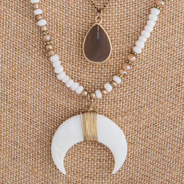 "Two layered beaded necklace featuring white, natural and gold beads, a teardrop pendant and a crescent detail. Approximately 24"" in length."