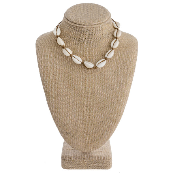 "Puka shell cord necklace with a lobster clasp closure. Approximately 16"" in length."