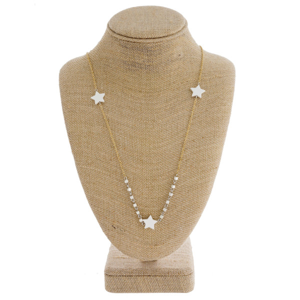 "Long gold chain necklace featuring square beads and star accents. Approximately 31"" in length."