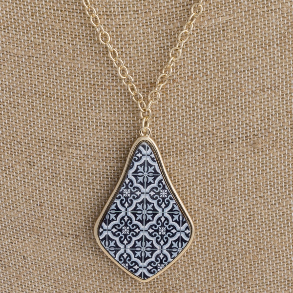 "Long metal necklace featuring a teardrop inspired wood pendant with pattern details and beaded accents. Pendant approximately 2"". Approximately 36"" in length overall."