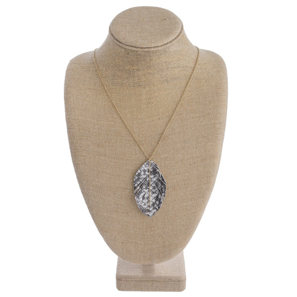 """Long metal necklace featuring faux leather snakeskin feathered inspired pendant with a gold metal accent. Pendant approximately 3"""". Approximately 36"""" in length overall."""