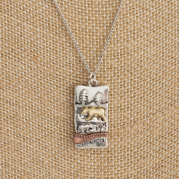 "Long metal necklace featuring a mama bear pendant with forest details. Pendant approximately 1"". Approximately 18"" in length."
