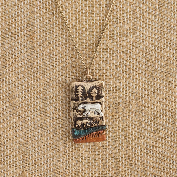 """Long metal necklace featuring a mama bear pendant with forest details. Pendant approximately 1"""". Approximately 18"""" in length."""