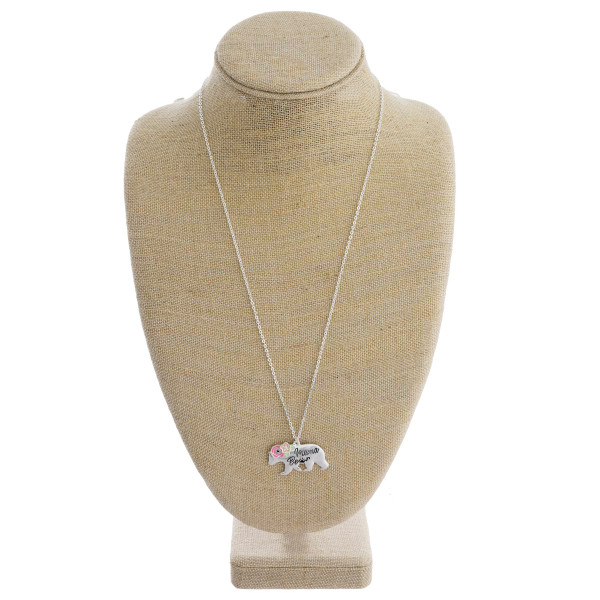 """Long metal necklace featuring """"mama bear"""" pendant with flower detail. Approximately 30"""" in length."""