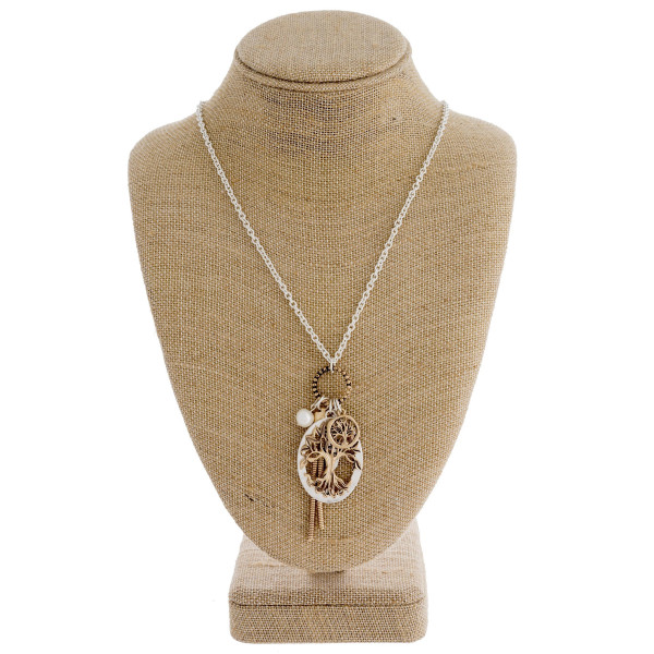 "Long silver chain necklace featuring a ""Tree of Life"" pendant with a pearl and tassel accent. Approximately 36"" in length."