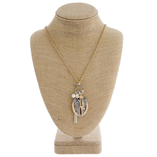 "Long gold chain necklace featuring an ""angel wing"" pendant with pearl and tassel accents. Approximately 36"" in length."
